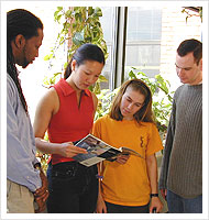 Four students look at magazine.