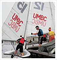 Man in life jacket stands in sailboat as he reaches towards second sailboat carrying two people. UMBC printed on sails.