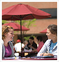 Two female students sitting at table outside and laughing.