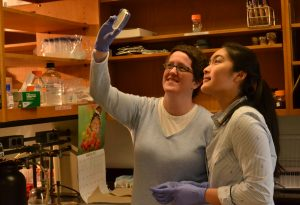 Dr. Erin Green holds petri dish up to light as her and student look through it.